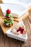 Brinquedos e bacia da palha do Natal com o abanador de sal na madeira Imagens de Stock Royalty Free