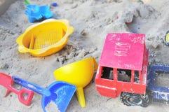 Brinquedos plásticos brilhantes de Children's na areia do sandpit Imagens de Stock Royalty Free