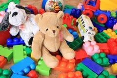 Brinquedos plásticos coloridos com cão e urso de peluche Fotografia de Stock