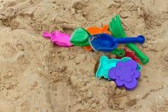 Brinquedos Varicolored na areia Foto de Stock Royalty Free