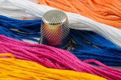 Brins de coton coloré et d'un dé Photographie stock