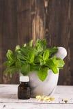 Brins, huile de menthe poivrée et pilules en bon état au-dessus de table en bois Image stock