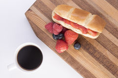 Brioche bun with strawberries, blueberries and raspberries. On a chopping board with black coffee royalty free stock images