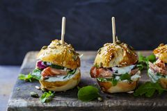 Brioche buns with salmon and salad. Multi seeded brioche buns with hot smoked salmon, cucumber, salad and yogurt sauce Royalty Free Stock Images