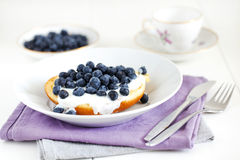 Brioche or english muffin with blueberries and cream Royalty Free Stock Images