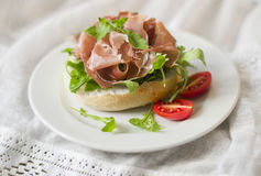 Brioche with prosciutto, arugula and cherry tomatoes on a white plate Royalty Free Stock Photos