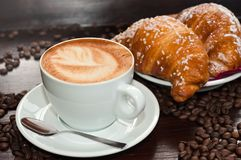 Brioches with cappuccino. Cappuccino with Brioches and coffee beans stock photo