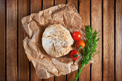 Brioches made with coriander seeds. Wholegrain brioches made with coriander seeds and tomatoes, served on paper and wooden tray; top view Royalty Free Stock Images