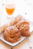 Brioches and orange juice for breakfast. Assorted sweet brioches on dish and fruit juice for morning breakfast Stock Images