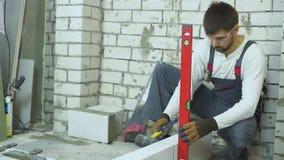 Brique de fixation de constructeur s'étendant avec le marteau en caoutchouc selon le niveau à bulle banque de vidéos