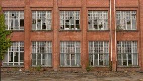 Brique wal avec les fenêtres cassées d'une école abandonnée Photos libres de droits