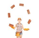 Briques de jonglerie de travailleur de la construction féminin d'isolement sur le CCB blanc Image stock
