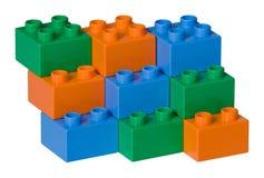 Briques en plastique bleues, vertes et oranges de jouet Images stock