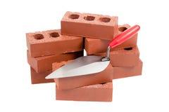 Briques et truelle d'un maçon Photos stock