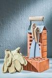 Briques et truelles verticales de gants de version sur le fond de concrette photo stock