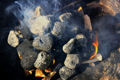 Briquette in a Grill. Briquette burning in a grill Stock Photo