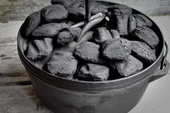 Briquettes d'Oven On Wooden Background And de Néerlandais de fonte images stock