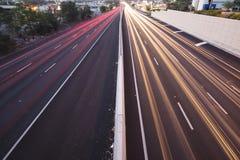 Brisbane, Austrália - quarta-feira 12, 2014: Passagem superior que olha na estrada pacífica - M1 com os carros que viajam na noit Fotografia de Stock Royalty Free