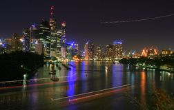 Brisbane City. River by night in Australia with light trails of boats and an airplane Royalty Free Stock Images