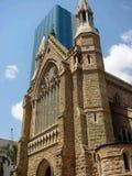 Brisbane-Kathedrale, die einen modernen Glaswolkenkratzer sich überlappt Stockbilder