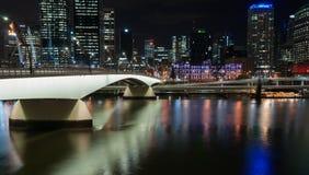 Brisbane Victoria Bridge iluminated tegen dark en stadsbuildi royalty-vrije stock foto