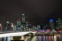 Brisbane Victoria Bridge iluminated tegen dark en stadsbuildi royalty-vrije stock afbeelding