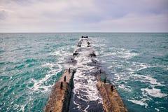 Brise-lames concret entrant profondément dans la mer images libres de droits