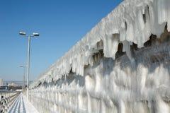 Brise-lames congelé avec des glaçons contre le ciel bleu photographie stock libre de droits
