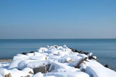 Brise-lames couvert de neige Photographie stock