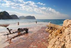 Brise-lames en pierre et vieille remorque de bateau Photo stock