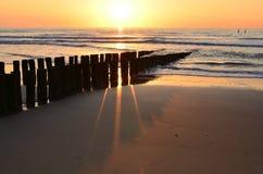 Brise-lames sur la plage dans le soleil de soirée   Photographie stock