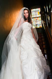 Brise in Staircase in Mansion Before Wedding. Bride on staircase with stained galss window in back Stock Photo