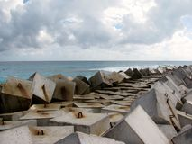 Briseur de vague fait de cubes concrets cancun mexico Photo stock