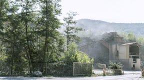 Briseur en pierre au pied d'une montagne de poussière minérale dans le processus de fabrication Image stock