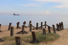 Briseurs sur la plage avec un bateau à l'arrière-plan Images libres de droits