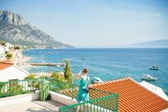 Brist, Dalmatien, Kroatien - eine Frau, die ein Foto der schönen Bucht von Brist macht lizenzfreies stockbild