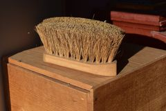 Bristle Brush. Old Fashioned bristle brush sitting on a wooden box royalty free stock photos