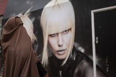 Bristol, Reino Unido, abril, 16, 2019: Uma mulher muçulmana nova esconde sua cara enquanto anda passado um quadro de avisos com u fotos de stock royalty free