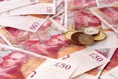 Británicos cincuenta billetes de banco de la libra y una pila de monedas Imagenes de archivo