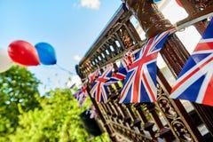 Británicos Union Jack que golpea banderas contra el cielo azul fotos de archivo