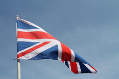 Brit flag flying high. Flag of Britain fluttering in the wind against a clear bright blue summer sky Royalty Free Stock Photo