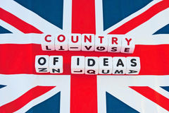 Britain country of ideas. Text 'country of ideas' uppercase letters inscribed on small white cubes placed on a background of the British Union Jack flag Royalty Free Stock Images