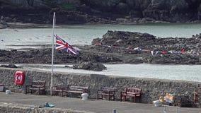Britannici inbandierano il halfmast d'ondeggiamento a Cemaes, Galles - Regno Unito archivi video