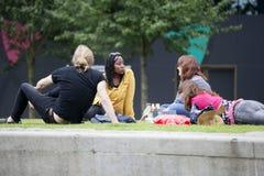 Briten, die oben nach der Arbeit auf Gras in Südufer in London kühlen Lizenzfreies Stockbild