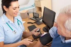 Briten-Krankenschwester, die Blutdruck des älteren Mannes nimmt Lizenzfreie Stockfotografie