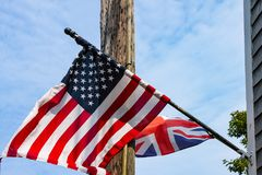 Briten und amerikanische Flaggen, die von einem verwitterten Schindelhaus vor einem elektrischen Pfosten und einem blauen bewölkt lizenzfreies stockbild