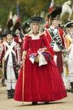 Britische Dame im roten Kleid passt mit Verachtung die britische Auslieferung zu General George Washington am 225. Jahrestag von  Lizenzfreie Stockfotografie