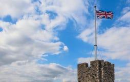 Britische Flagge, die über einen Schlossturm steigt Stockbilder