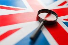 BRITISCHE Flagge, die durch eine Lupe schaut Die Studie der Geschichte und der Kultur der Leute des großen Landes von England lizenzfreie stockbilder