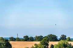 Britische Landschaft der Sonnenuntergangansicht nahe Northampton mit nationalem Aufzugturm und Fliegen baloon lizenzfreies stockbild